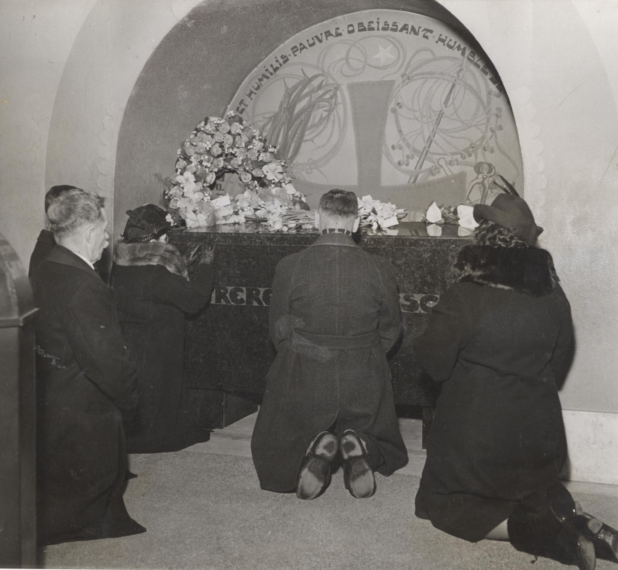 Pèlerins à genoux devant le tombeau de frère André dans la crypte.